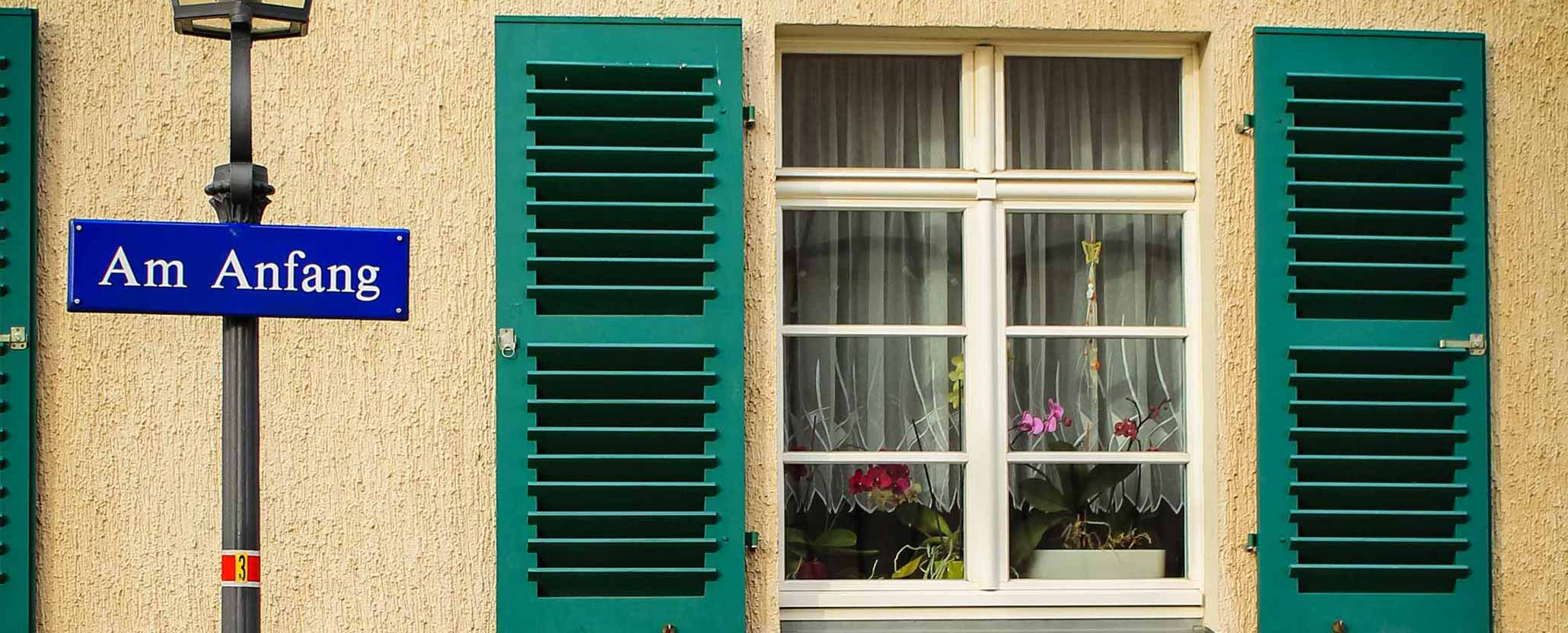 """Eine Hausfassade mit grünen Fensterläden, davor ein Straßenschild mit der Aufschrift """"Am Anfang"""""""