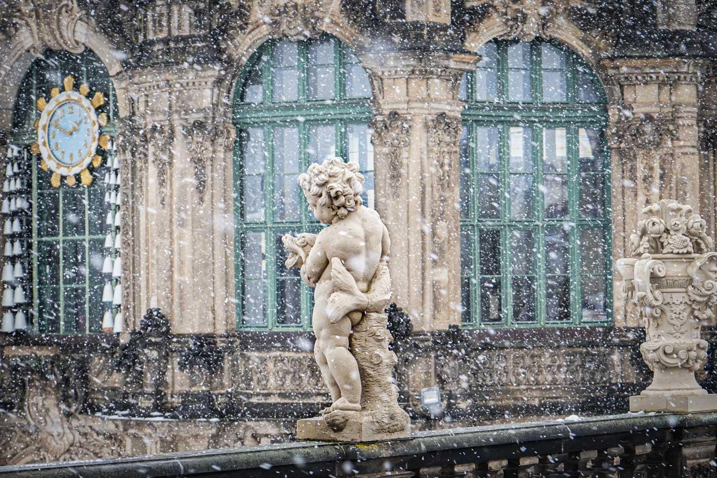 Eine Sandsteinfigur des Dresdner Zwingers im Schneegestöber. Im Hintergrund ist das Glockenspiel zu sehen.