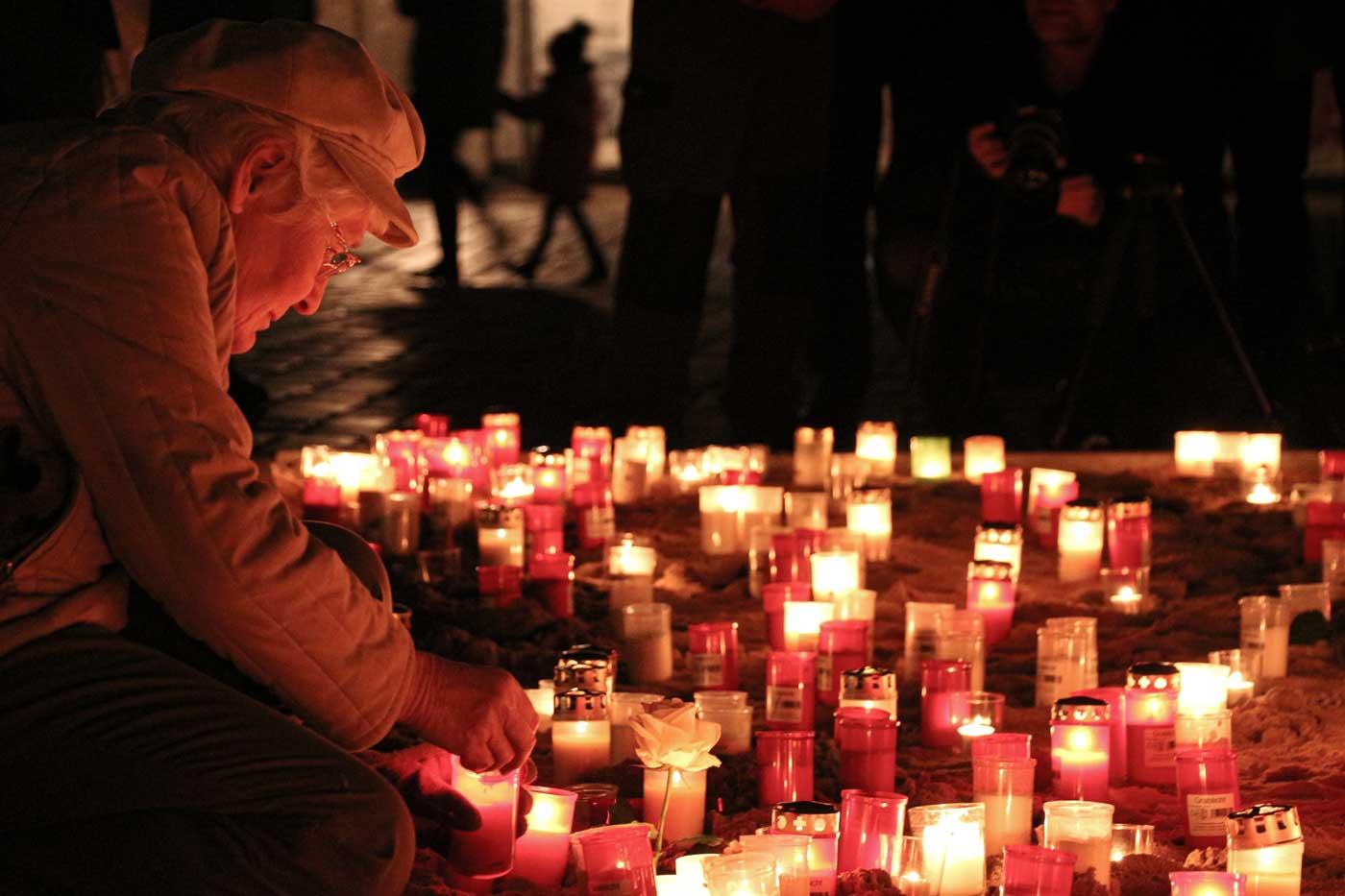 Eine ältere Frau legt zum Gedenken vor der Frauenkirche Blumen nieder und zündet eine Kerze an. Sie erinnert damit an die Zerstörung der Stadt am 13. Februar 1945.