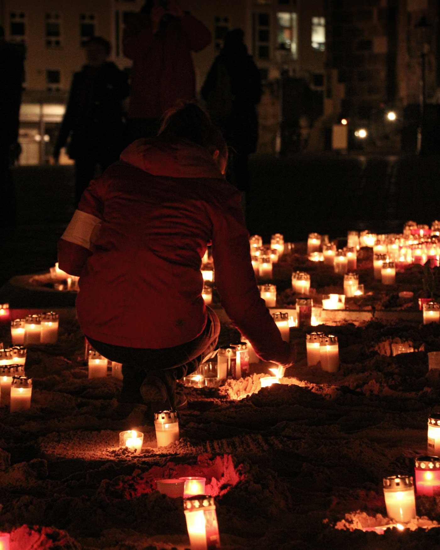 Eine junge Frau zündet eine Kerze vor der Frauenkirche an und erinnert an die Zerstörung Dresdens am 13. Februar 1945.